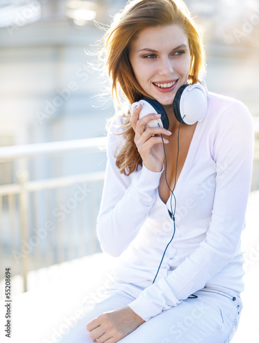 Delightful young woman holds the headphones