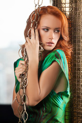 Woman with chain. Beautiful young red hair woman holding chains