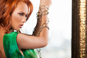 Woman in chain. Beautiful young red hair woman in chain looking