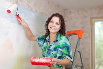 Happy woman paints wall