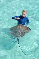 Tourist playing with stingray in a lagoon