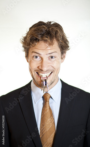 Smiling businessman holding keys between his teeth
