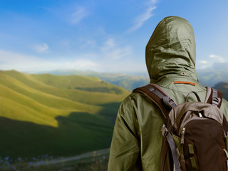 Hiker with backpack standing on top of a mountain and enjoying n