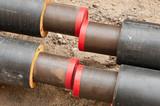 Neue Fernwärmerohre in einer Baugrube bereit zur Montage