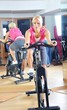 Beautiful woman doing exercise in a spinning class at gym