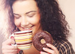 Woman holding donut and coffee in hand