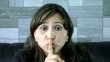 closeup of woman making a hush gesture