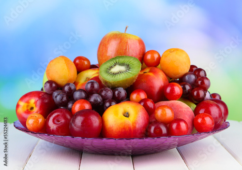 Assortment of juicy fruits on wooden table, on bright