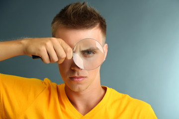 Young man looking through magnifying glass on grey background