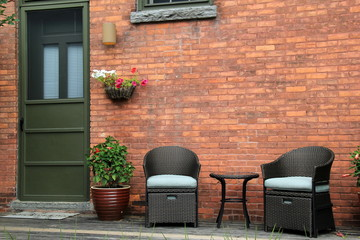 Comfy chairs and potted plants on front porch