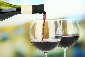 Red wine being poured into wine glass, on bright background