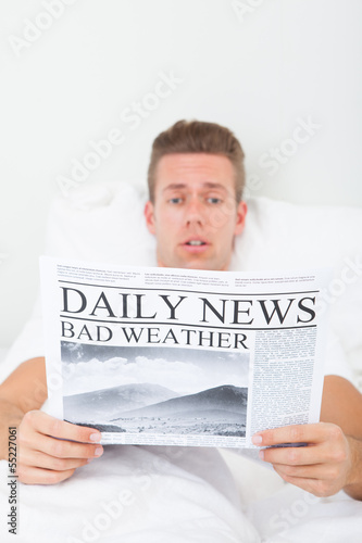 Shocked Young Man Lying On Bed Reading Newspaper