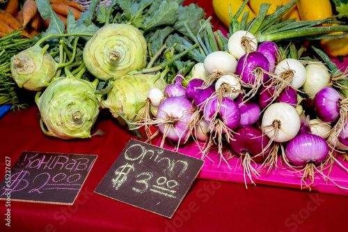 Kohlrabi and onions on display for sale at a local farmers marke