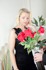 Man presenting a woman with red roses