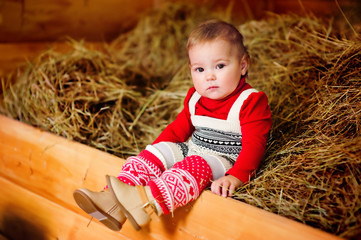 baby girl in fashion clothes sitting on a hay