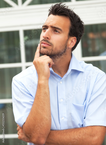 Thoughtful young businessman in front of his office