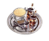 Turkish tea in a glass cup on a tray, chocolate spoons