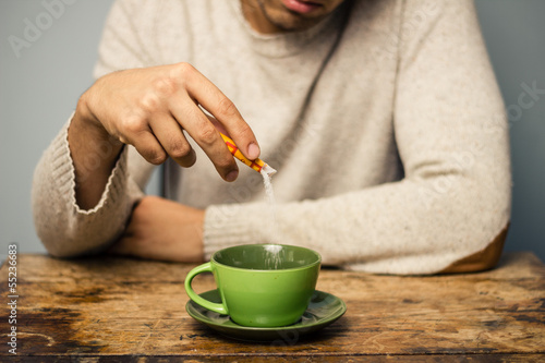 Man adding sugar to his coffee or tea