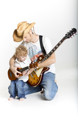 Father and son are playing guitars