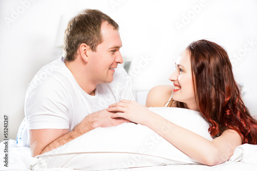 Young man and woman lying together in bed