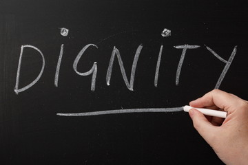 Writing the word Dignity on a blackboard
