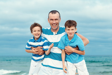 father and sons walking on beach
