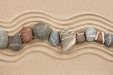 Striped stones on the sand - 55244412
