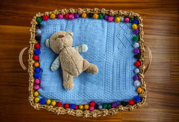 teddy bear on basket/bed ready for a newborn