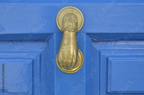 Old metal door handle knocker on wooden background