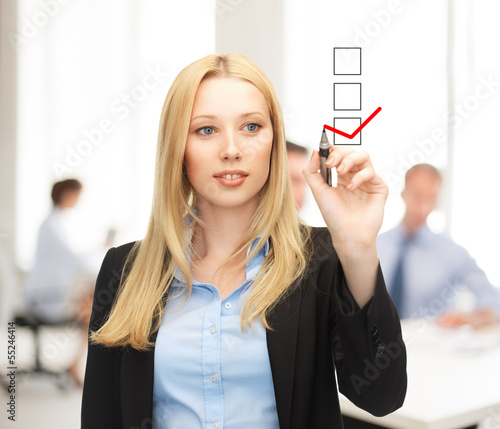 businesswoman drawing checkmark on virtual screen