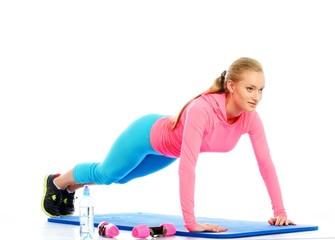 Beautiful girl doing push-ups on a floor mat