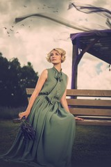 Woman in long green dress sitting on a bench