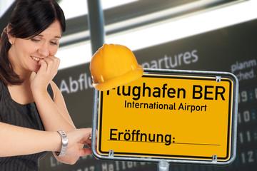 verzweifelte Frau und Schild - Flughafen Berlin Brandenburg