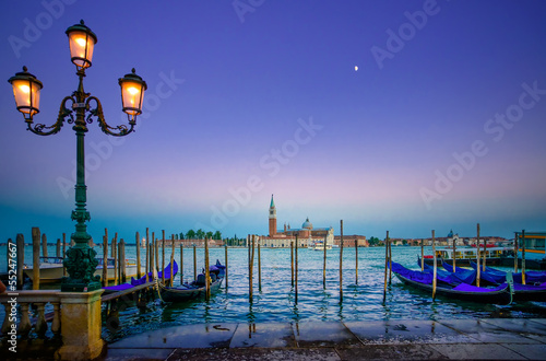 Venice, street lamp and gondolas on sunset and church. Italy