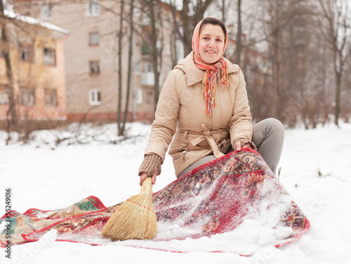woman cleans red rug with snow