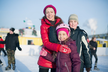 A mother with two children standing on outdoor rink
