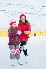 Happy mother and daughter mold snowballs at outdoor skating rink