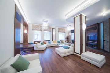 The spacious, well lit living room with round glass table