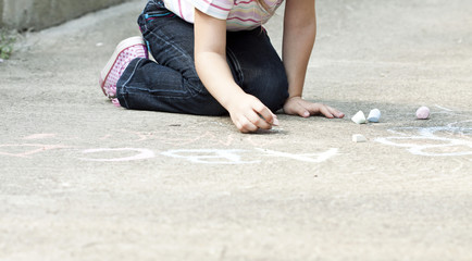 Back to school concept girl drawing with chalk in the schoolyard