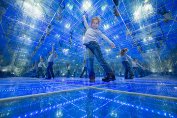 Smiling little girl standing in a mirrored room