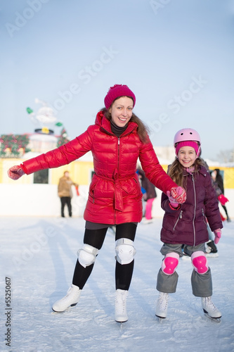 mother and daughter are skating at outdoor skating rink