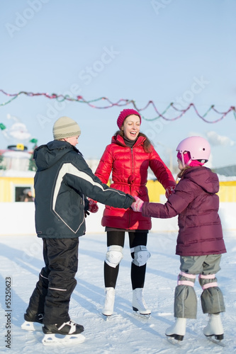 A mother with children are skating on outdoor skating rink