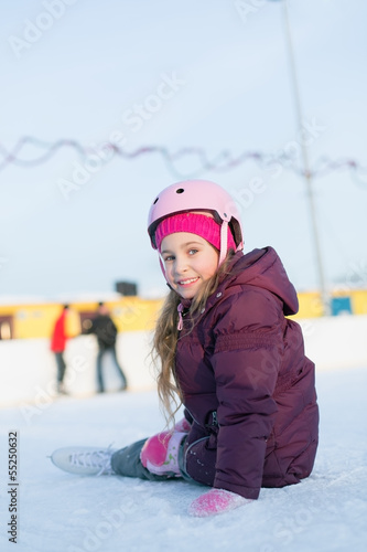 Smiling little girl in helmet and knee pads sitting at rink