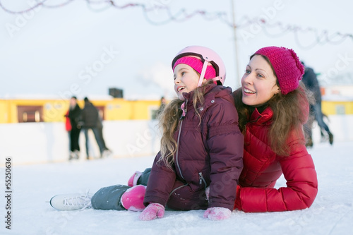 Happy mother and daughter sitting on the outdoor rink