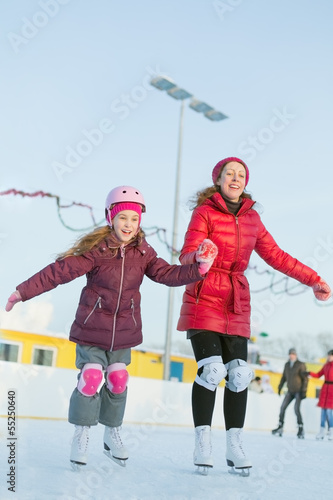 Happy mother and daughter are skating at the outdoor skating rin