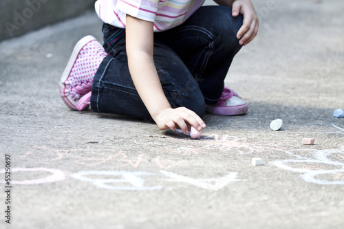 Back to school concept girl drawing with chalk on the schoolyard