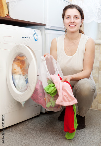 woman  putting clothes  in to washing machine