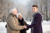 young man greets an elderly couple in park in winter