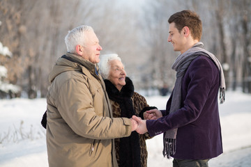 Young man wearing a scarf greets an elderly couple
