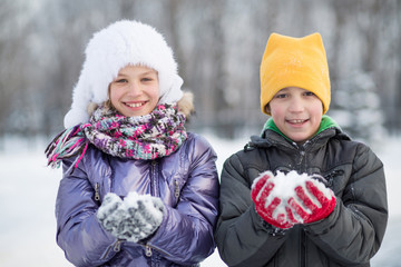 smiling boy with girl in hat playing with snowballs in winter